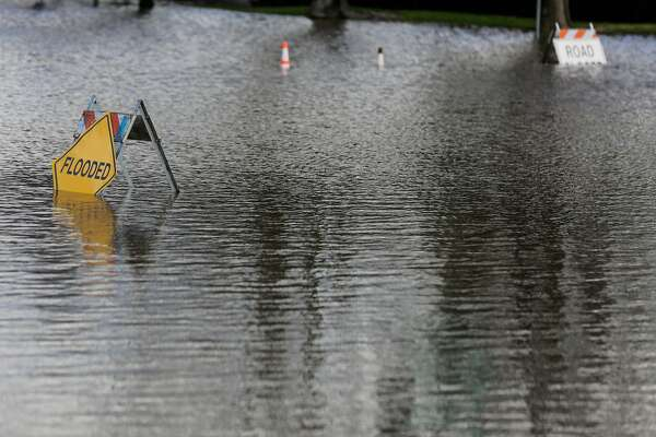 Signs for flooding are seen at the site of a severe flood which caused many people to evacuate their homes in San Jose, California, on Tuesday, Feb. 21, 2017.