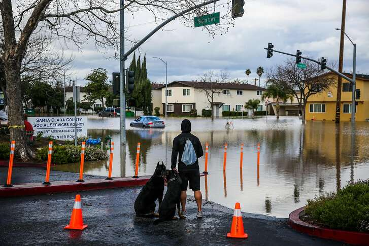 Jimmy Quilenderino looks at the devastation caused by severe flooding on Senter street in San Jose, California, on Tuesday, Feb. 21, 2017.