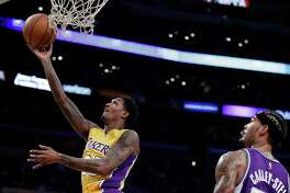 Los Angeles Lakers' Lou Williams shoots as teammate Tarik Black, center, and Sacramento Kings' Willie Cauley-Stein watch during the first half of an NBA basketball game, Tuesday, Feb. 14, 2017, in Los Angeles. (AP Photo/Jae C. Hong)