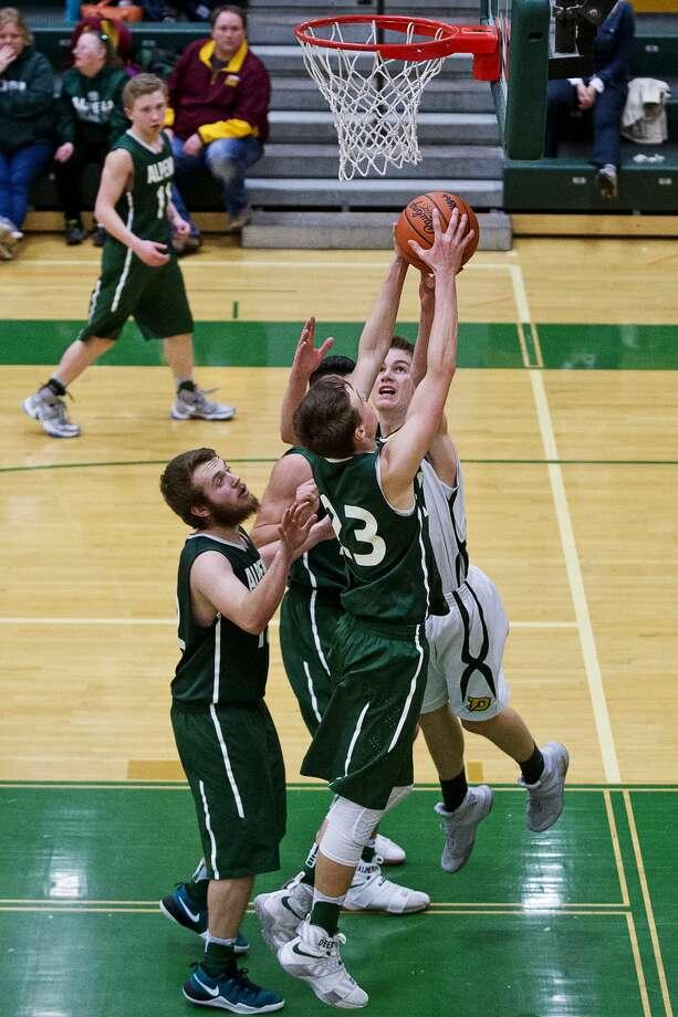 Dow's Isaac Moolenaar and Alpena's Cam Decaire reach for the rebound on Tuesday at H. H. Dow High School. Photo: Erin Kirkland/Midland Daily News/Erin Kirklamd