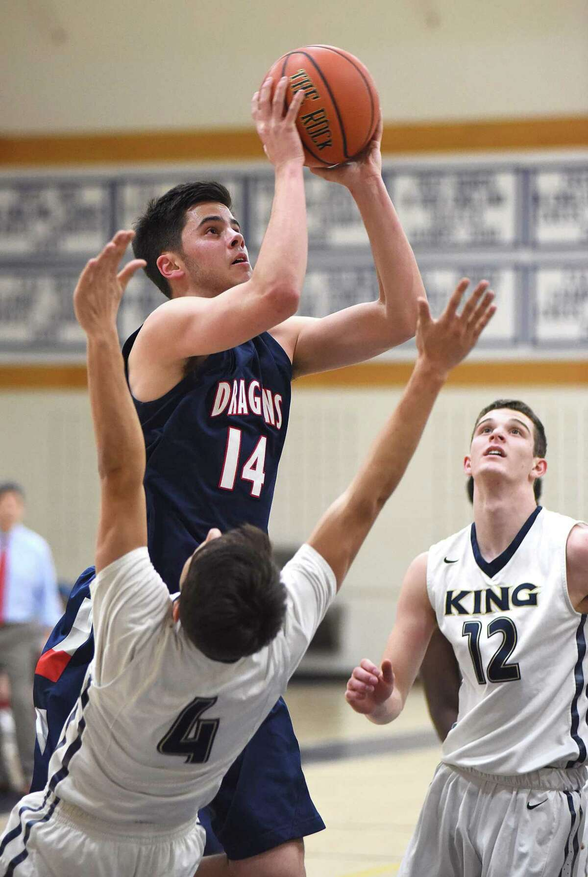GFA's Greg Lawrence, top, puts up a shot over King's Trey Canevari, left, as Renn Lints looks on during Tuesday's FAA quarterfinal game at Coyle Gymnasium in Westport.