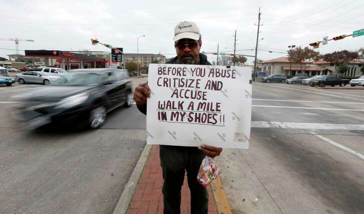 A panhandler stands on a median at San Felipe and Voss Streets in Houston on Dec. 24, 2015.  (Karen Warren / Houston Chronicle )