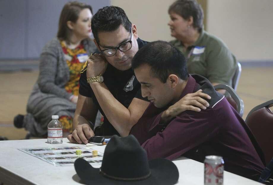 San Antonio police officer Jesse Mermella  plays a game with Ricky Hodgson (right) at the event. Photo: John Davenport /San Antonio Express-News / ©San Antonio Express-News/John Davenport