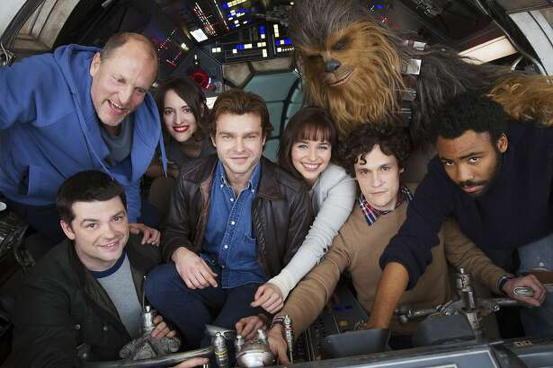 """In this undated image provided by Lucasfilm, cast members and co-directors of the Han Solo """"Star Wars"""" spin-off pose for a photo, from bottom left, co-director Christopher Miller, Woody Harrelson, Phoebe Waller-Bridge, Alden Ehrenreich, Emilia Clarke, Joonas Suotamo as Chewbacca, co-director Phil Lord and Donald Glover. The Walt Disney Co. announced Tuesday, Feb. 21, 2017, that shooting began at London's Pinewood Studios on Monday. (Jonathan Olley/Lucasfilm via AP)"""