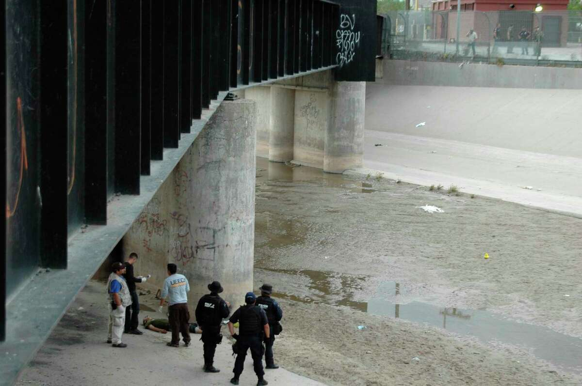 Mexican authorities examine the body of Sergio Hernandez under the Paso Del Norte border bridge as U.S. officials, at right, watch in 2010. Some justices described this concrete culvert as a no-man's land.