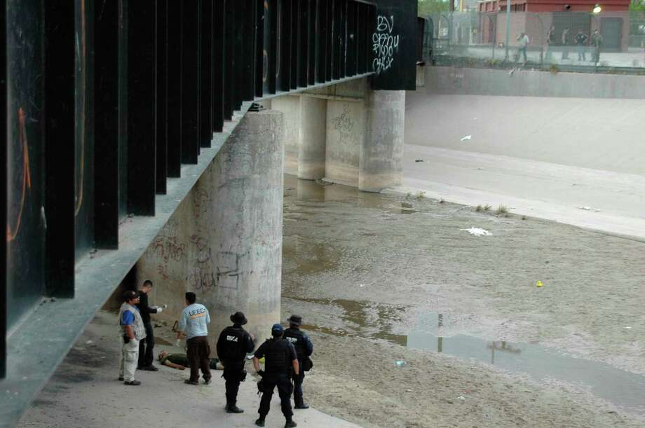 Mexican authorities examine the body of Sergio Hernandez under the Paso Del Norte border bridge as U.S. officials, at right, watch  in 2010. Some justices described this concrete culvert as a no-man's land. Photo: STR / AP2010