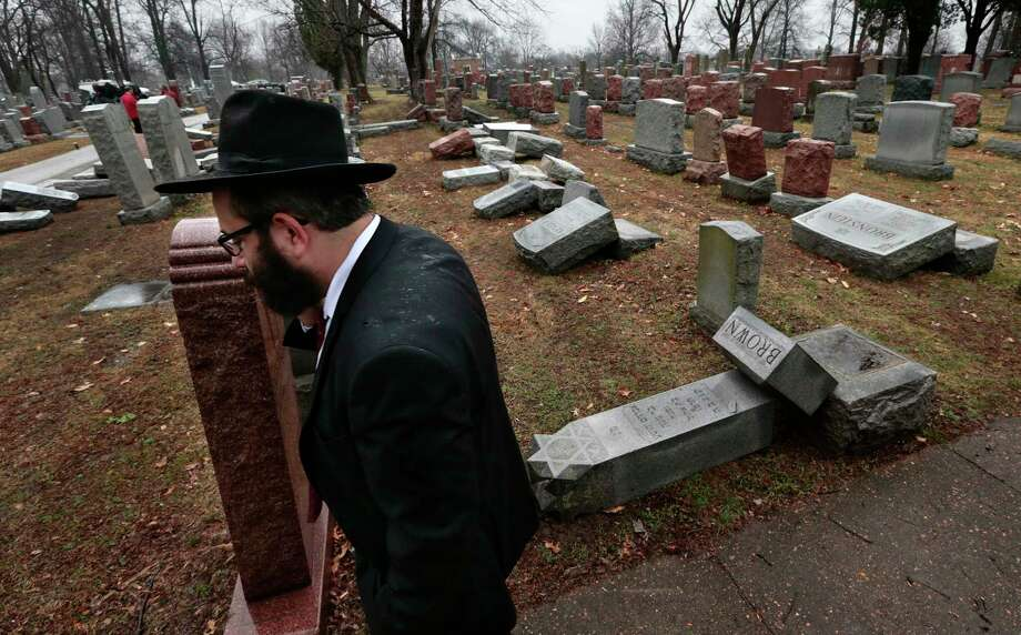 """Rabbi Hershey Novack walks through Chesed Shel Emeth Cemetery in University City, Mo., where almost 200 gravestones were vandalized late Sunday. """"People who are Jewish are shocked and angry,"""" Novack said. Photo: Robert Cohen, MBI / St. Louis Post-Dispatch"""
