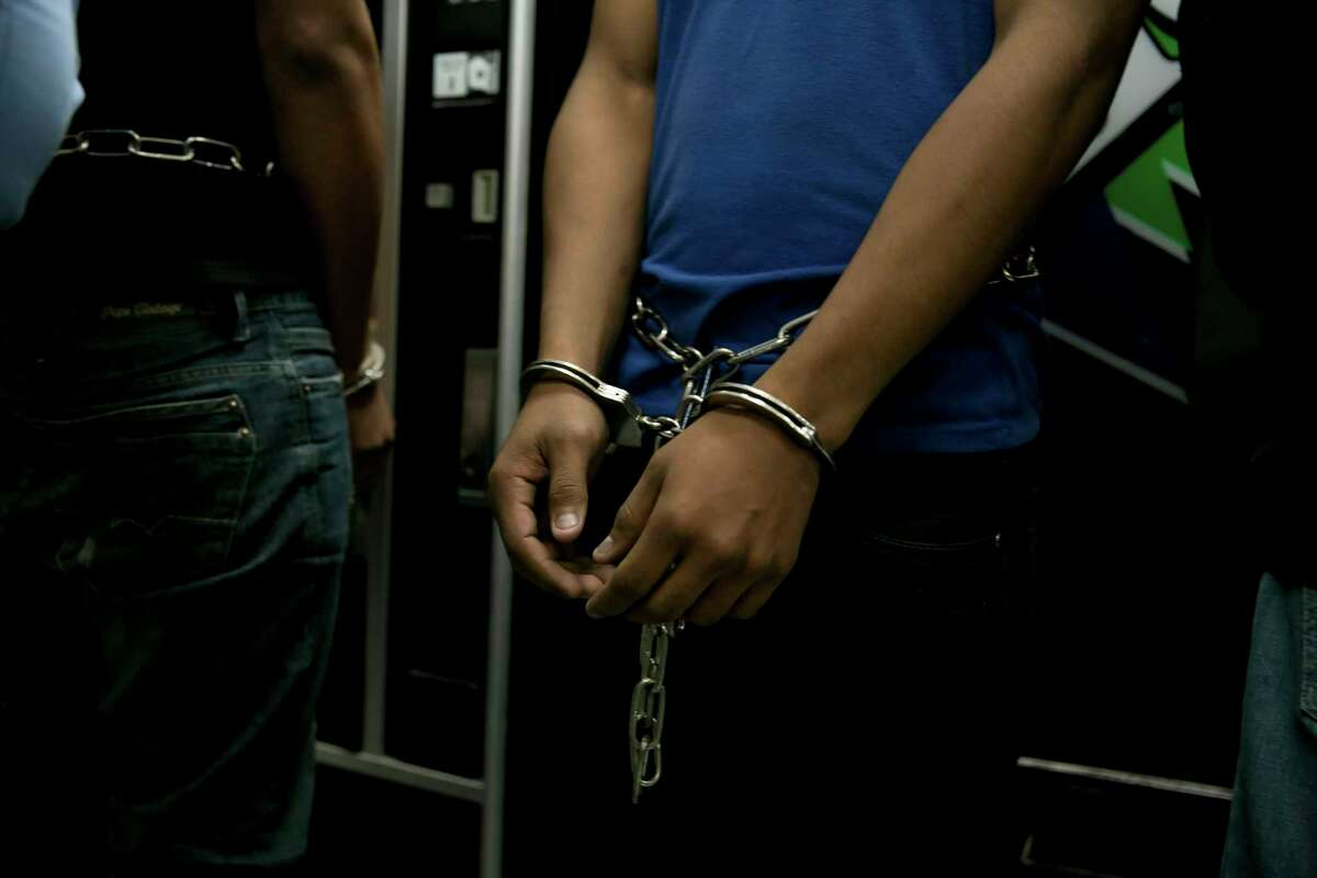 Men facing deportation are handcuffed at a Border Patrol station in Brownsville in March 2014 before being flown to Honduras via Miami.