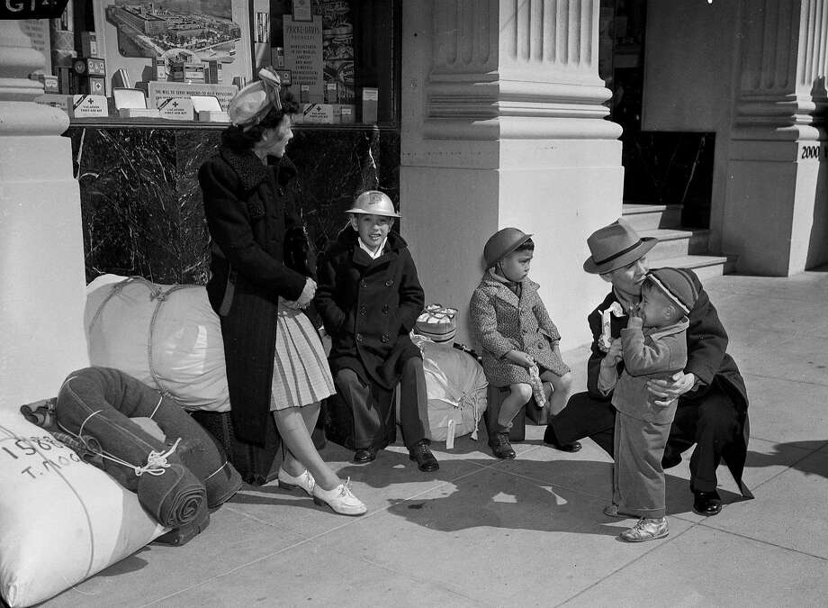 A San Francisco family of Japanese descent waits near the SFPD Northern Station on April 6, 1942before heading to a U.S. internment camp during World War II. They are identified as Mr. and Mrs. Joe Miyamoto, with their sons, Donald, Philip and Keith. Photo: Chronicle File Photo, The Chronicle