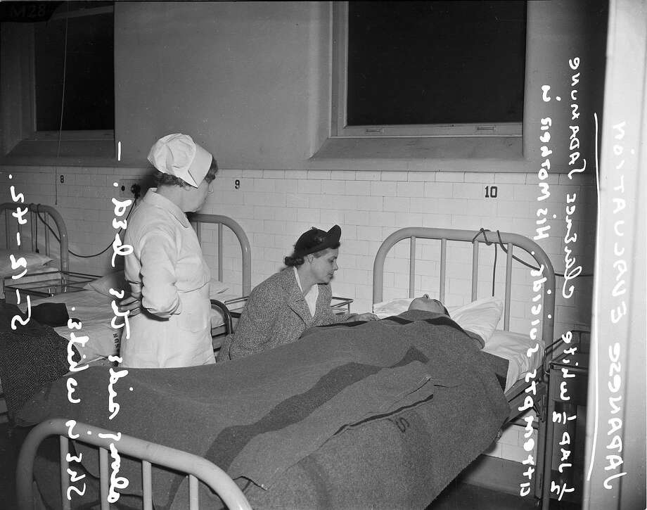 April 6, 1942: The caucasian mother of Japanese-American U.S. citizen Clarence Sadamune sits at the 21-year-old's hospital bedside, after Sadamune tried to commit suicide. Photo: Chronicle File Photo, The Chronicle