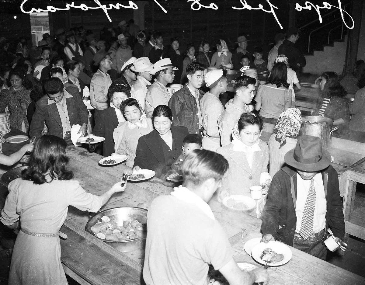 In September of 1942, California citizens of Japanese descent eat one of their last meals at Tanforan Park, before boarding a train from the Bay Area internment camp to another camp in Utah.