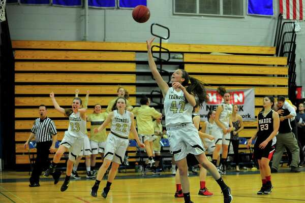 Trumbull's Brady-Ayn Lynch releases a shot in the final second of triple overtime as teammates rush onto the court after beating Fairfield Warde during FCIAC Girls Basketball Semi-final action in Fairfield, Conn., on Tuesday Feb. 21, 2017.