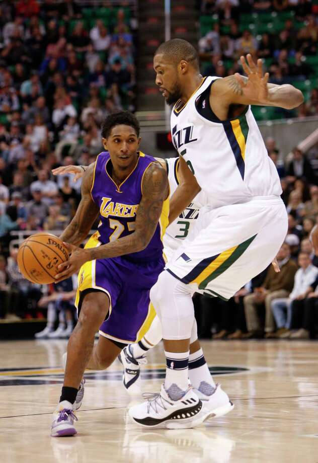 Los Angeles Lakers' Lou Williams (23) drives the basket as Utah Jazz's Derrick Favors, right, defends in the first half of an NBA basketball game Thursday, Jan. 26, 2017, in Salt Lake City.  Photo by Kim Raff Photo: Kim Raff, FRE / FR159054 AP