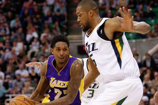 Los Angeles Lakers' Lou Williams (23) drives the basket as Utah Jazz's Derrick Favors, right, defends in the first half of an NBA basketball game Thursday, Jan. 26, 2017, in Salt Lake City.  Photo by Kim Raff