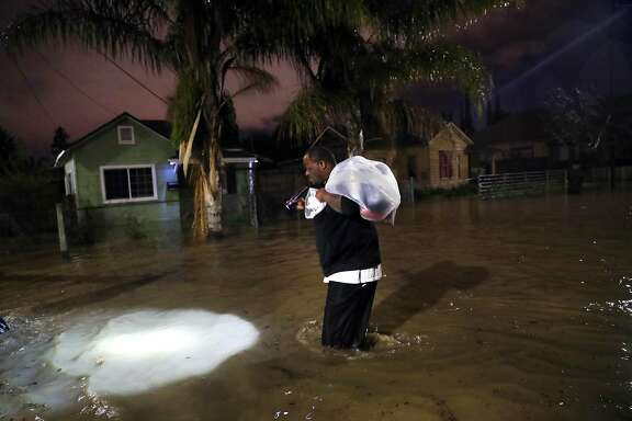 As floodwaters overtake his street, Dominic Clark evacuates his home as the swollen Coyote Creek floods 21st Street in San Jose, Calif., on Tuesday, February 21, 2017.