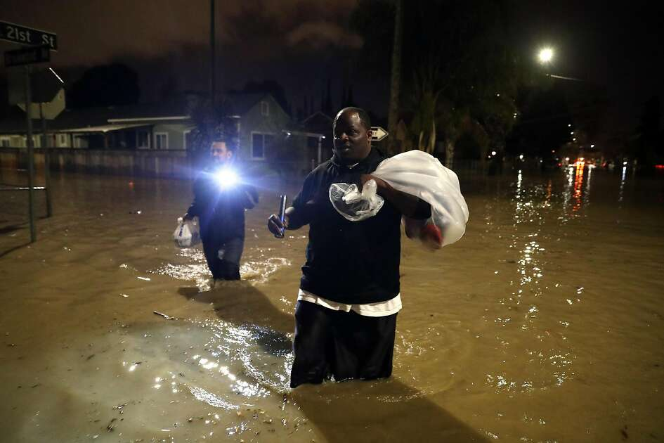 As floodwaters overtake his street, Dominic Clark and Paul Madrigal evacuate their homes as the swollen Coyote Creek floods 21st Street in San Jose, Calif., on Tuesday, February 21, 2017.