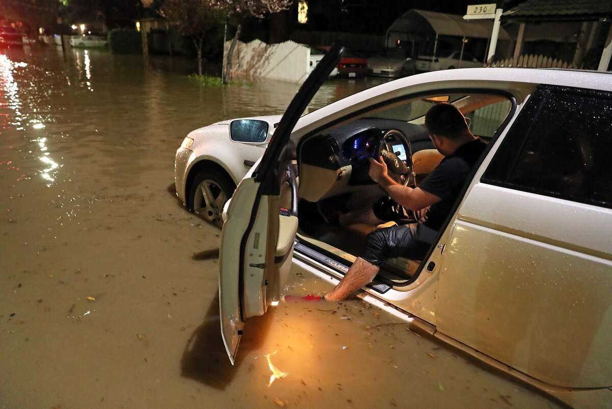 Leone Chavez tries to start his car before pushing it to dry land as the swollen Coyote Creek floods 21st Street in San Jose, Calif., on Tuesday, February 21, 2017.