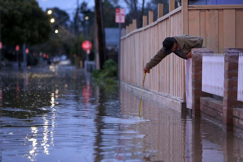 Raul Aladorre measures the water depth on Brookwood as the swollen Coyote Creek floods the street near his home on 22nd Street in San Jose, Calif., on Tuesday, February 21, 2017. Photo: Scott Strazzante, The Chronicle
