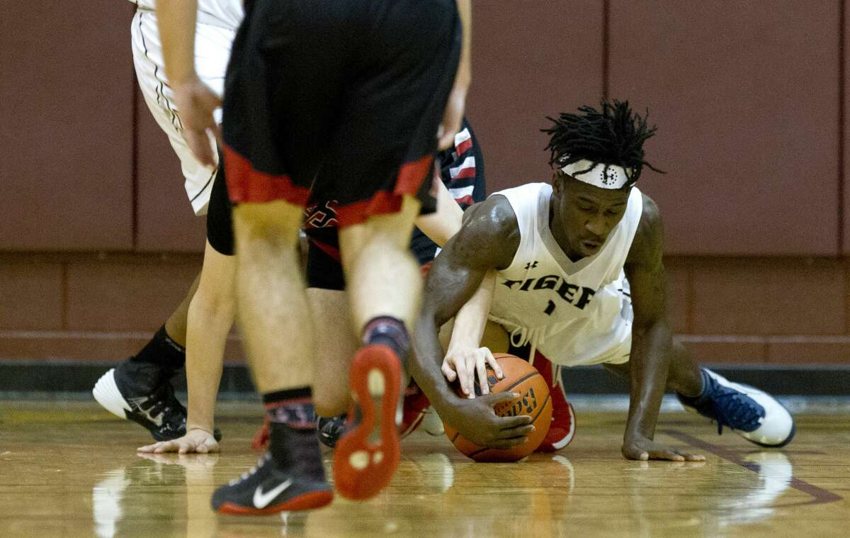 Conroe guard Jay Lewis (1) dives on a loose ball during the first quarter of a Region II-6A high school basketball bi-district playoff game at Johnson Activities Center Tuesday, Feb. 21, 2017, in Fairfield. Conroe defeated Rockwall-Heath 74-71.