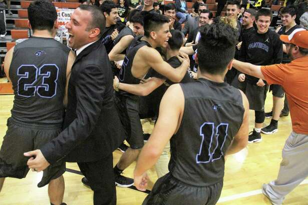 United South players celebrate with head coach Carmelo Gonzalez after beating McAllen Nikki Rowe 56-53 Tuesday in Alice to snap a streak of four straight opening-round losses.