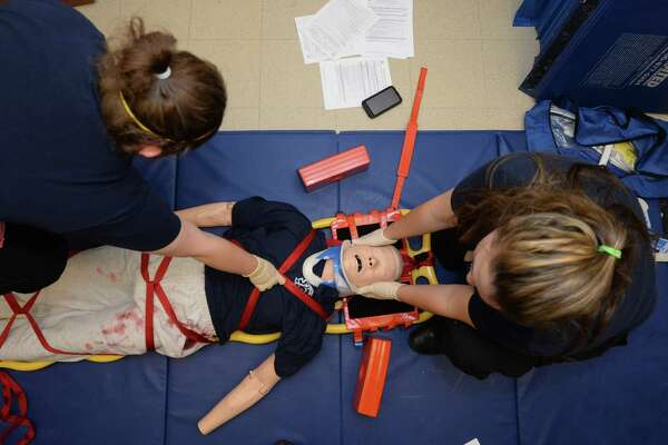From left, Helen Curl and Sarah Duke practice a spinal immobilization during a paramedic class at Lamar Institute of Technology Tuesday.  Due to low pay and long training hours, the number of local paramedics is declining. Photo taken Tuesday, February 21, 2017 Guiseppe Barranco/The Enterprise