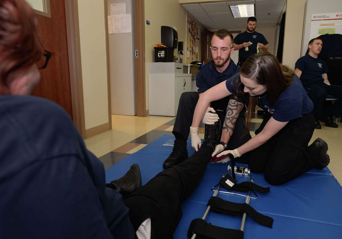 From left, Eric Watson and Ashley Rogers practice working a leg injury on Shaiona Edington during a paramedic class at Lamar Institute of Technology Tuesday. Due to low pay and long training hours, the number of local paramedics is declining. Photo taken Tuesday, February 21, 2017 Guiseppe Barranco/The Enterprise