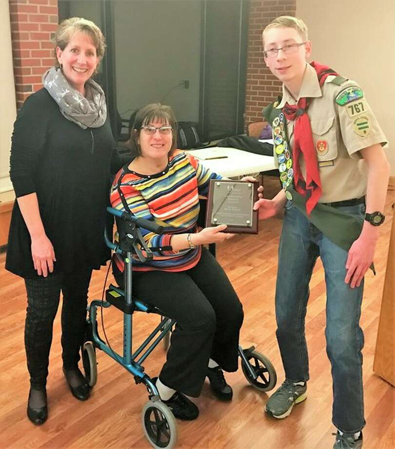 Kathy Allen, executive director of Personal Assistance Options, left, and Melissa Andrus, center, present the PAO Community Impact Award to Nick Feige of Boy Scout Troop 767, during PAO's annual meeting in Midland.