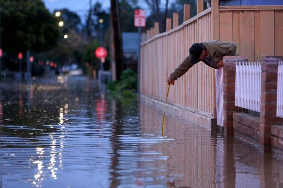 Raul Aladorre measures the water depth on Brookwood as the swollen Coyote Creek floods the street near his home on 22nd Street in San Jose, Calif., on Tuesday, February 21, 2017.