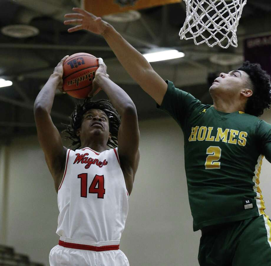 Wagner's Justice Tolbert (14) goes for a shot against Holmes' Tylen Figueroa (02) in Class 6A bi-district basketball playoffs at Alamo Convocation Center on Tuesday, Feb. 21, 2017. (Kin Man Hui/San Antonio Express-News) Photo: Kin Man Hui, Staff / San Antonio Express-News / ©2017 San Antonio Express-News