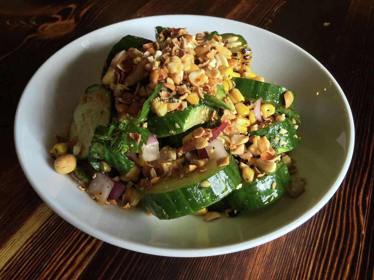 Cucumber appetizer at Alchemy Kombucha and Culture also includes diced red onions, corn, candied peanuts and a drizzle of toasted chile oil.