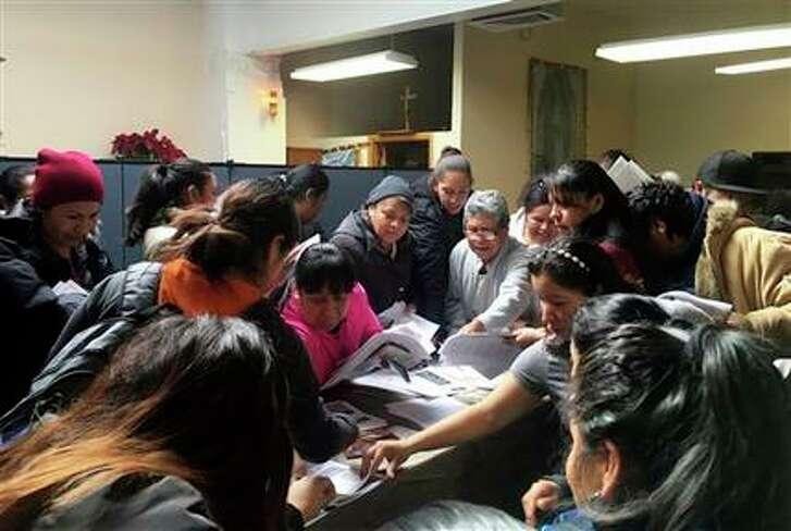 Miembros de la comunidad mexicana toman hojas de información entregadas por miembros del consulado mexicano en Nueva York en la iglesia de Saint Andrews, en Yonkers, Nueva York, el lunes 13 de febrero de 2017. Según los Servicios de Inmigración y Control de Aduanas, Nueva York y otras áreas fueron el objetivo de redadas recientemente. (AP Foto/Claudia Torrens)