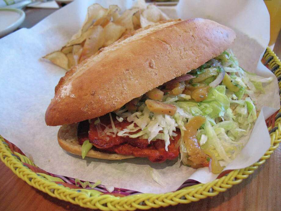 The torta al pastor comes with marinated pork, pineapple, red onion salad, lettuce and avocado cream. Photo: Express-News File Photo / San Antonio Express-News