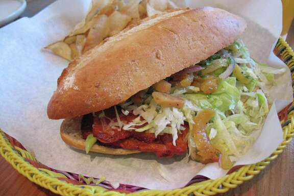 The torta al pastor comes with marinated pork, pineapple, red onion salad, lettuce and avocado cream.