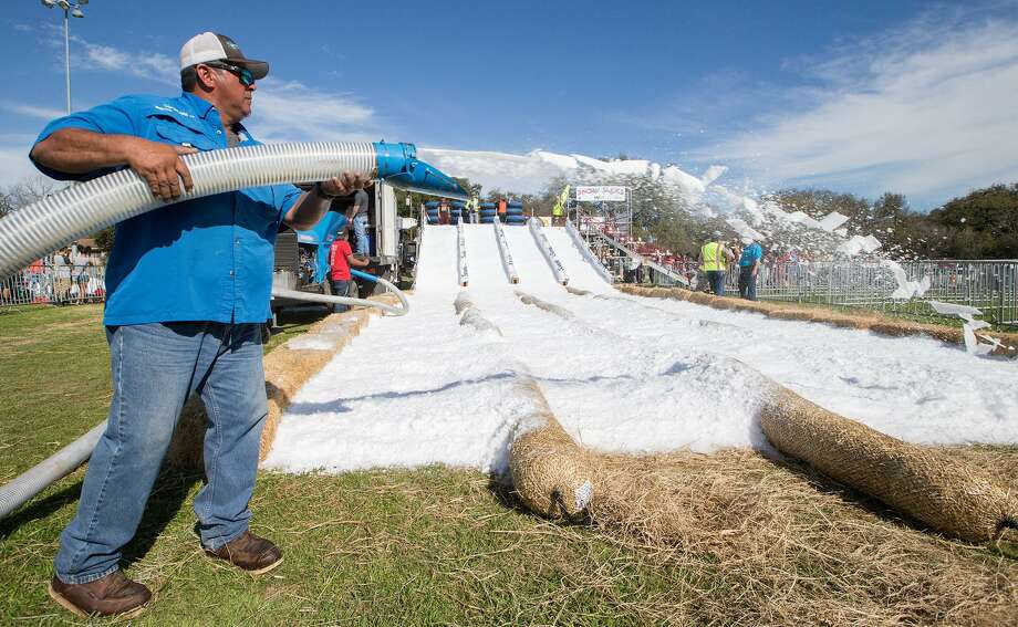 Jimmy Garcia with Mireles Party Ice blows crushed ice on the Snow Slide runs before the start of Universal City's 8th annual Snowfest & Carnival at Universal City Park on Saturday, Feb 18, 2017. Photo: Marvin Pfeiffer / San Antonio Express-News / Express-News 2017