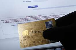 A picture taken on February 5, 2013 in Nice shows a person holding an American Express credit card in front of a computer screen displaying an internet website which bears a warning message against fraud . French police has arrested, early this morning in Paris and in several French and overseas departments, 22 people in connection with the trade of credit cards numbers on internet. AFP PHOTO / VALERY HACHE        (Photo credit should read VALERY HACHE/AFP/Getty Images)