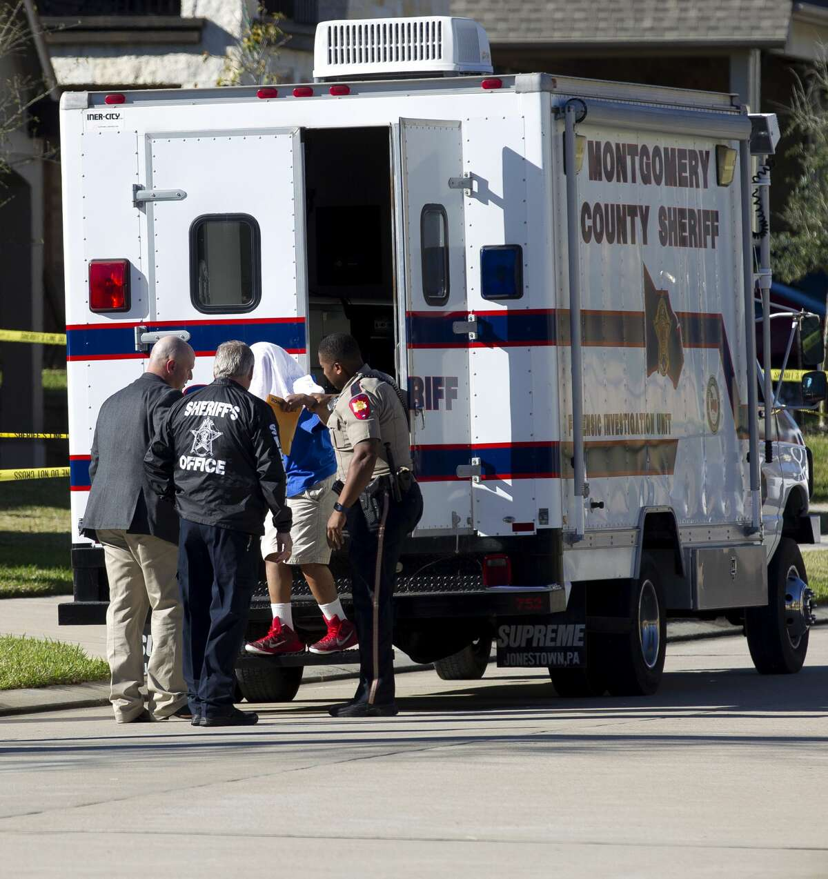 Personnel with the Montgomery County Sheriff?•s Office take a boy who called 911 after his father stabbed his mother to death from the scene on Chestnut Meadow Court Wednesday, Feb. 22, 2017, in Conroe. An MCSO officer shot and killed the man that stabbed his wife to death after approaching officers.