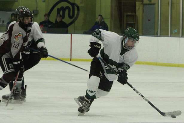 The New Milford High School boys' ice hockey team recently faced off against Milford. The final score was 9-1, with New Milford taking home the win. Above, sophomore Zach Hook makes play on the ice.