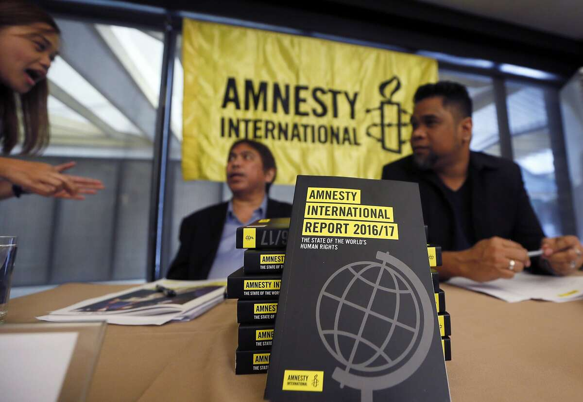 A reporter, left, talks to Amnesty International, Philippines' Jose Noel Olano and Wilnor Papa, right, following the release of the 2016/17 Amnesty International report which they released at a news conference Wednesday, Feb. 22, 2017, in suburban Quezon city northeast of Manila, Philippines. Amnesty International says