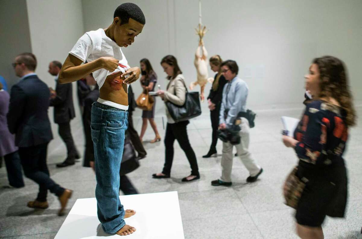 People walk past Ron Mueck's
