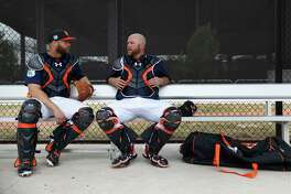 Houston Astros catchers Evan Gattis (11) and  Brian McCann (16) chat in a dugout during spring training at The Ballpark of the Palm Beaches, in West Palm Beach, Florida, Wednesday, February 22, 2017.
