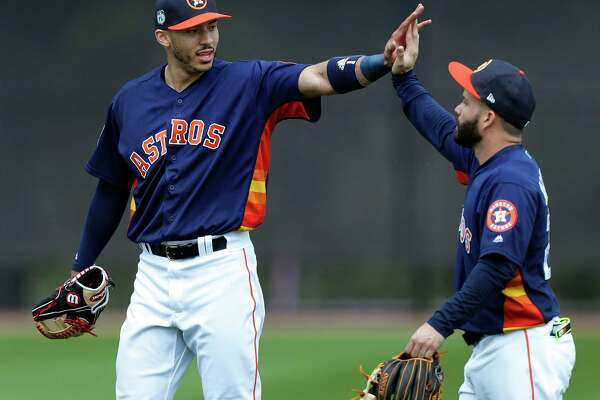 Houston Astros second baseman Jose Altuve (27) high fives Carlos Correa (1) after infield practice during spring training at The Ballpark of the Palm Beaches, in West Palm Beach, Florida, Wednesday, February 22, 2017.