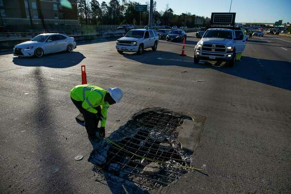 A contractor measures a massive pothole, which ended up measuring 10 feet by 7 feet, in the middle of I-45 North that has closed all but two lanes just north of the Hardy Toll Road Wednesday, Feb. 22, 2017 in Spring.