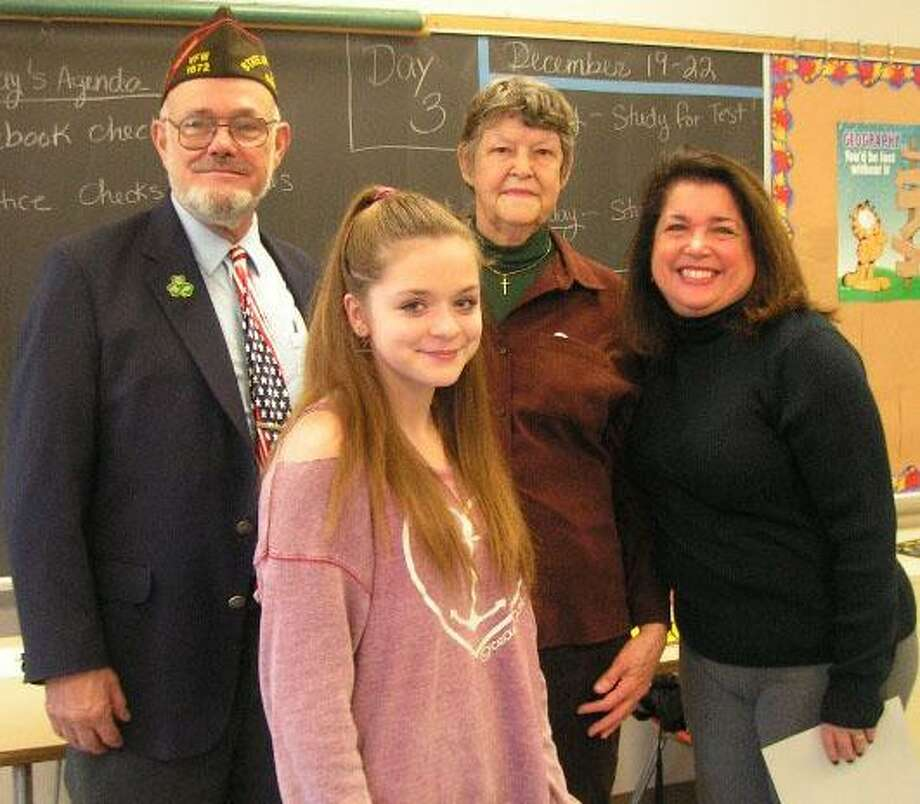 New Milford VFW Post 1672 Commander James Delancy, left, congratulates Patriot Pen VFW Post 1672 and district essay winner Kerith Bradshaw, a student at Schaghticoke Middle School, for placing first on the local level. They are joined by Pat Brought, post auxiliary president, second from right, and SMS teacher Keli Solomon. Photo: Courtesy Of VFW Post 1672 / The News-Times Contributed