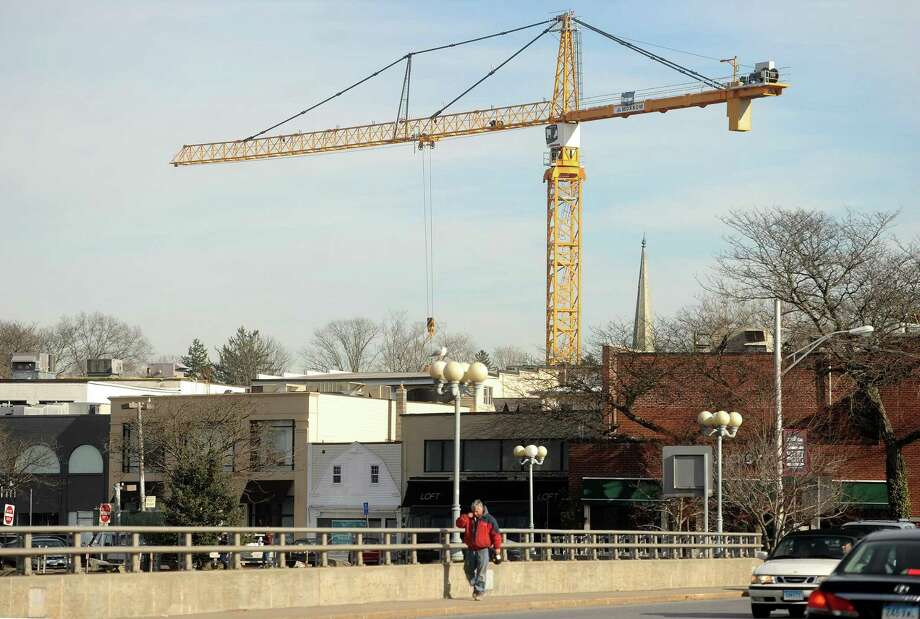 A giant crane hangs over downtown Westport during the construction of the Bedford Square retail development on the site of the old Westport YMCA on Church Lane. Photo: Brian A. Pounds / Hearst Connecticut Media / Connecticut Post