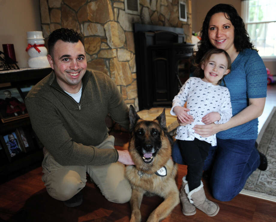 From left; Monroe Police Officer Jeff Loomis, his retired partner K-9 Gunner, daughter Kayla, 2, and wife Lynne at their home in Trumbull, Conn. on Wednesday, February 22, 2017. The dog recently retired after serving for six years as a K9 officer for the Monroe police department. Photo: Brian A. Pounds, Hearst Connecticut Media / Connecticut Post