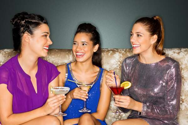 Beautiful female friends with cocktail drinks smiling together in nightclub. Horizontal shot.