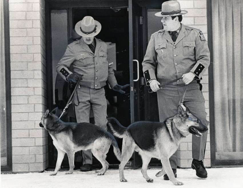 State Police member John Curry (right) leads his police dog Crow outside at the 1980 Winter Olympics in Lake Placid. Curry retired in 2003 as the chief technical sergeant in charge of canine units statewide. (New York State Police)