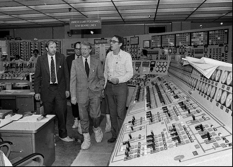 Wearing protective boots, President Carter, center right, accompanied by Dr. Harold Denton, then Director of the U.S. Nuclear Agency, left, and then Pennsylvania Gov. Dick Thornburg, left-rear, tour the control room of the Three Mile Island nuclear plant in Middletown, Pa. in this April 1, 1979 black-and-white file photo, four days after the nuclear accident.  Photo: AP