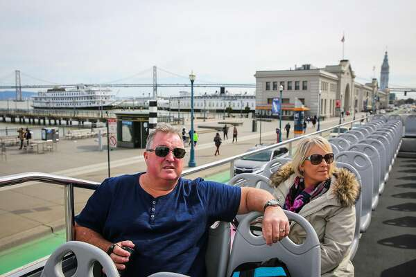 (l-r) Tourists Owen Mulligan and Leanne Mulligan, of Sydney, Australia listen as tour guide Rey Zegri (not pictured) points out Coit Tower during a City Sightseeing bus tour in San Francisco, California, on Wednesday, Feb. 22, 2017.