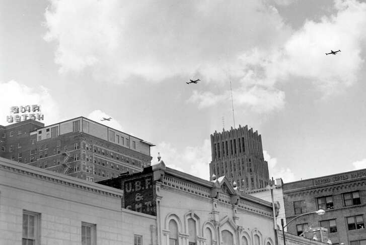Civil Defense drill, June 14, 1954. What appears to be P-80s are flying over downtown Houston. This view appears to have been taken at Preston and Milam.